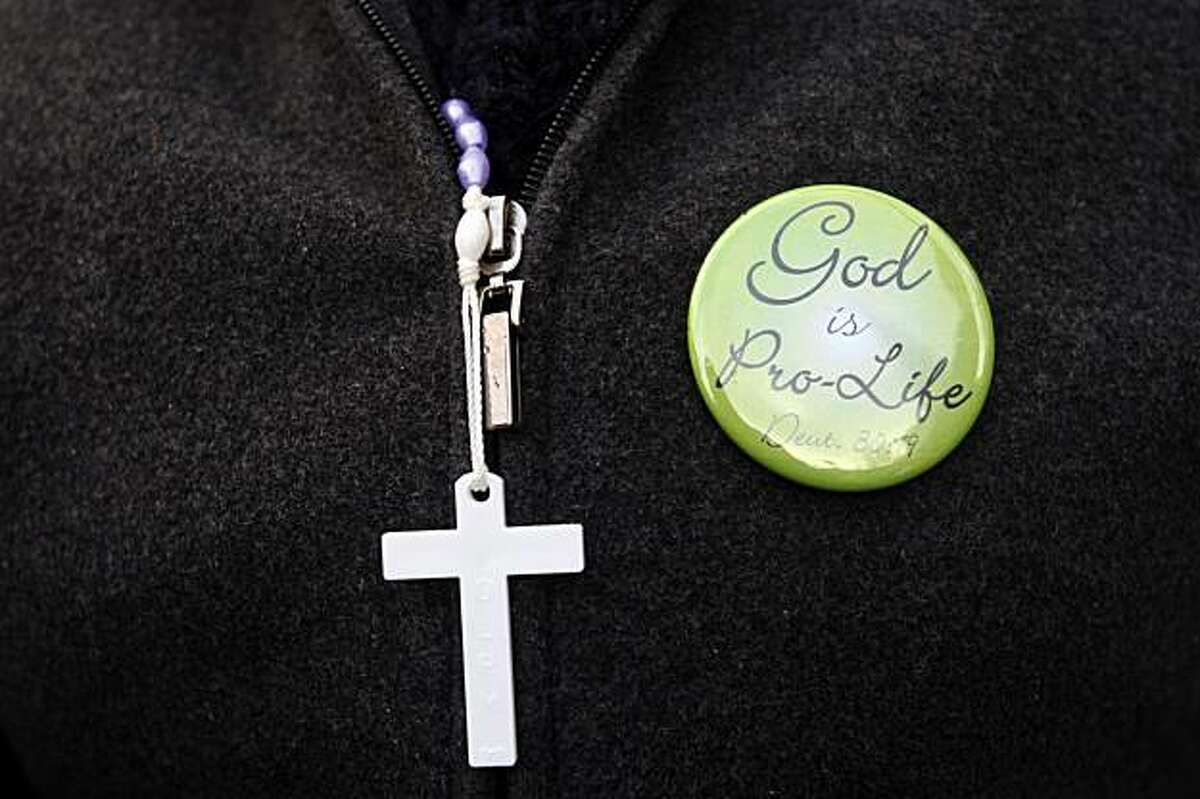 A participant in the Walk for Life wears a cross and a pin to express her position on abortion during the march in San Francisco on Saturday.