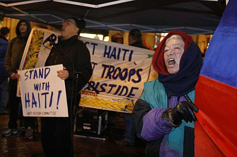 Adrianne Aron of Berkeley (right) holds the National Flag of Haiti as she sings along with other demonstrators during a song led by Dave Welsh (background left) during an emergency demonstration for Haiti, sponsored by the Haiti Action Committee, in San Francisco, Calif. at Market and Powell Streets on Monday, January 25, 2010.  Demonstrators called for the U.S. to alter it's aid to Haiti and the return to power of former Haitian president Jean-Bertrand Aristide. Photo: Lea Suzuki, The Chronicle