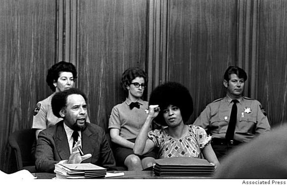 Angela Davis raises her fist to give her power salute as she sits in the courtroom at Marin Civic Center in San Rafael, Ca., on March 16, 1971. Davis, who is accused of supplying some of the weapons used in a shoot-out during an attempted escape of prisoners at the Marin County Courthouse, is waiting for her court hearing to start after it was postponed because of bomb threats. In the fall of 1970, she was on the FBI's Ten Most Wanted List. (AP Photo) Photo: Associated Press