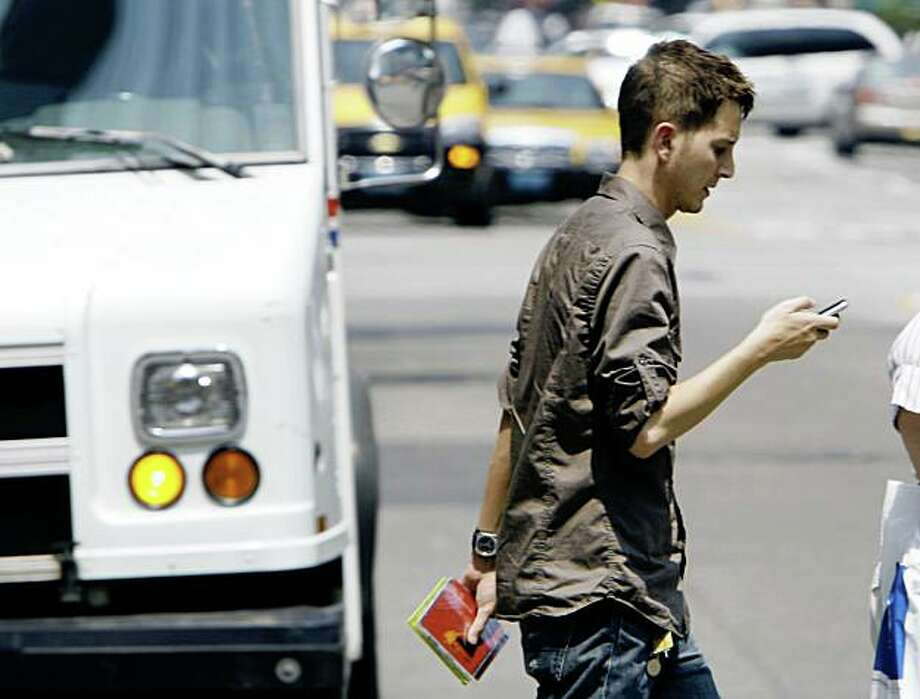Giancarlo Yerkes, a 30-year-old advertising employee, crosses a street in downtown Chicago while text-messaging with his cell phone, Tuesday, July 29, 2008. In an alert issued this week, the American College of Emergency Physicians says based on reports from emergency-room doctors around the country, the number of text-messaging pedestrians, bicyclists, roller-bladers and even motorists who aren't so fortunate is rising. Terkes admitted he once walked straight into a stop sign while texting and bumped his head. (AP Photo/M. Spencer Green) Photo: M. Spencer Green, AP