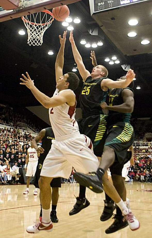 Stanford guard/forward Landry Fields drives to the basket past Oregon's E.J. Singler and Jeremy Jacob, from left, at Stanford's basketball game against Oregon in Palo Alto on Saturday. Photo: Adam Lau, The Chronicle