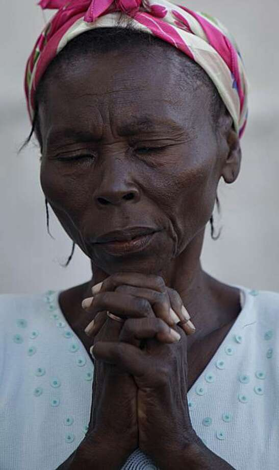 A woman prays during mass held outside the main Cathedral in Port-au-Prince, Sunday, Jan. 17, 2010.  The Cathedral was destroyed in Tuesday's earthquake. Photo: Gregory Bull, AP