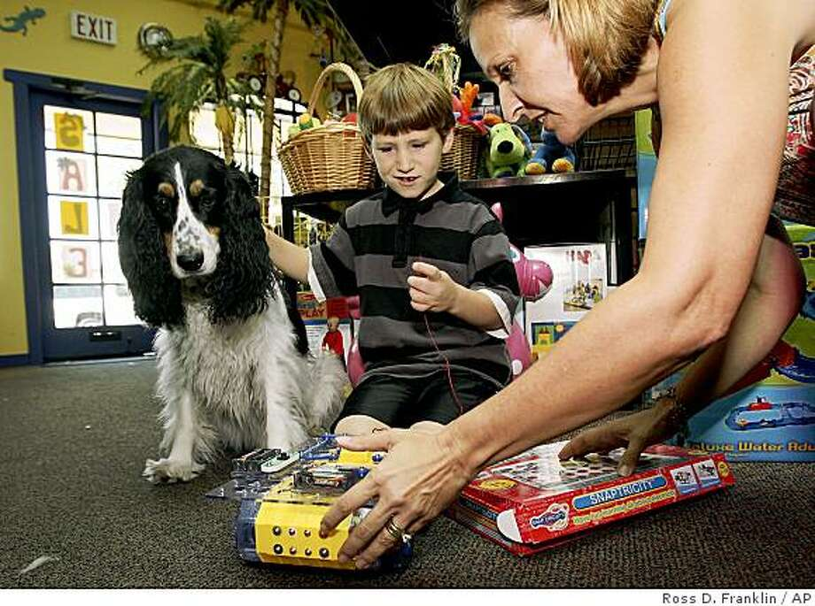With the help Kate Tanner, right, president of Kidstop, Elijah Michael Price, 7, of Woodland Park, Colo., middle, checks out a new toy, as McGuire, an English Springer Spaniel, looks on at Kidstop Educational Toys and Books store Thursday, July 24, 2008, in Scottsdale, Ariz.  At Kidstop, which offers mostly European brands as Haba and Corolle, 10 percent price hikes have already begun, according to owner Kate Tanner.  (AP Photo/Ross D. Franklin) Photo: Ross D. Franklin, AP