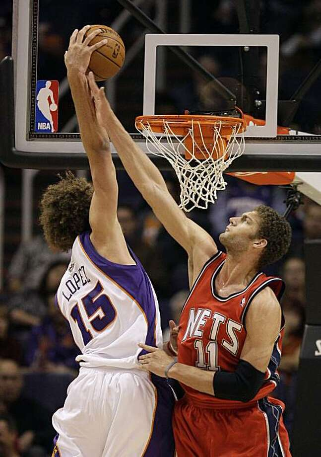 Phoenix Suns' Robin Lopez (15) dunks over his twin brother New Jersey Nets' Brook Lopez (11) in the first quarter in an NBA basketball game Wednesday, Jan. 20, 2010, in Phoenix. Photo: Ross Franklin, AP