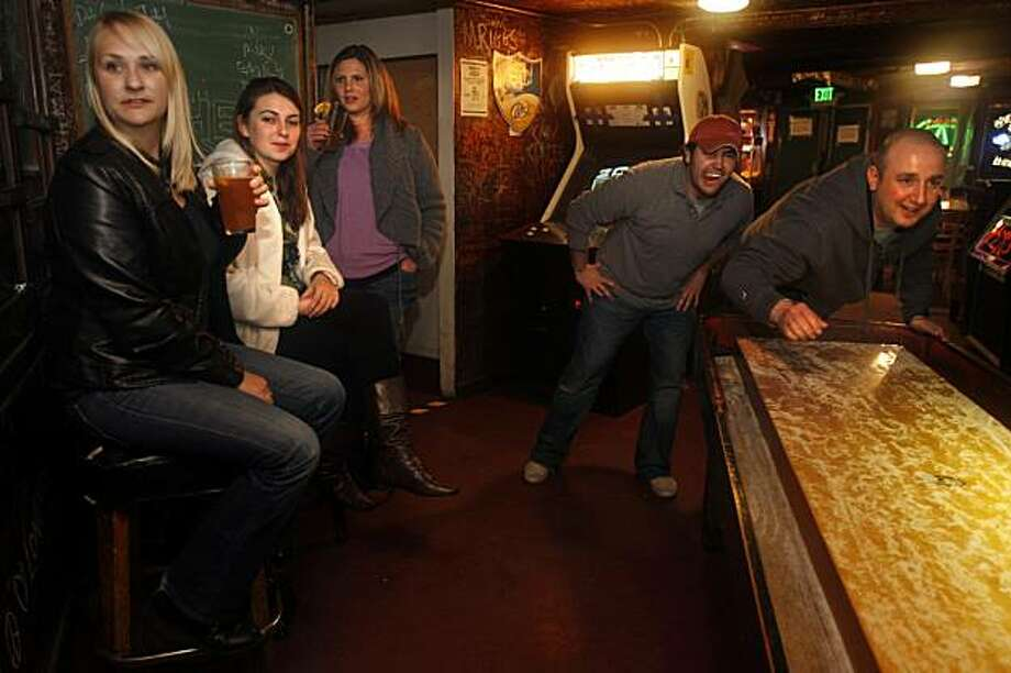 left to right--Uta Lorenzen from Oakland, Eva Miekus from Oakland, Amanda Turney from Alameda, Chris Rascon from Oakland,  and Doug Sakellariou (right) from Concord, at the Kingfish Pub & Cafe playing shuffleboard at a 1940's legendary full-length, 22-foot table in Oakland, Ca., on Thursday, January 7, 2010. Photo: Liz Hafalia, The Chronicle