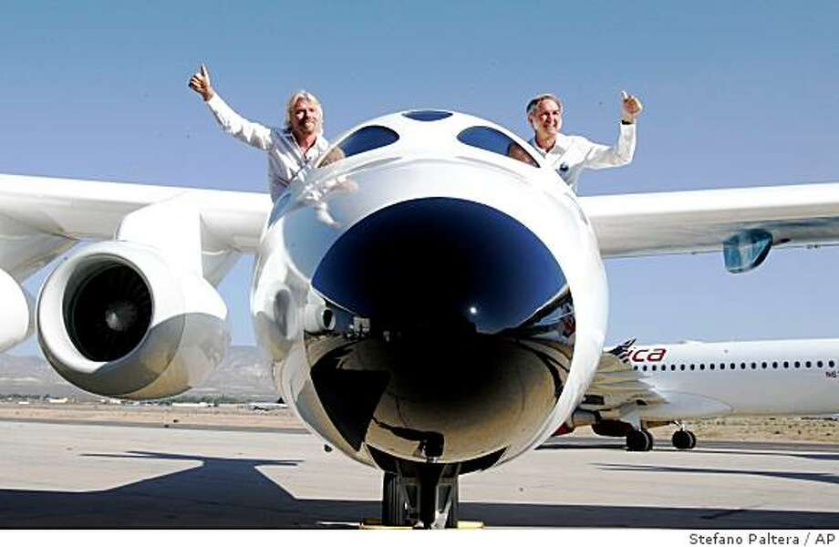 "Virgin Galactic founder Sir Richard Branson, left, and Scaled Composites LLC founder Burt Rutan wave from the mothership aircraft White Knight Two ""Eve"" during an unveiling ceremony at Scaled Composites hangar in Mojave, Calif. Monday, July 28, 2008.  More than 250 customers have paid $200,000 or put down a deposit for the chance to be one of Virgin Galactic's first space tourists. A date for the first launch has yet to be announced.  (AP Photo/Stefano Paltera) Photo: Stefano Paltera, AP"
