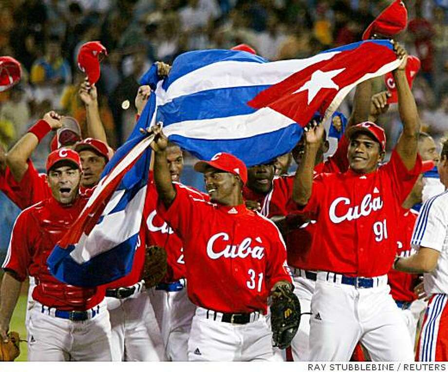 Ran on: 08-26-2004 Exuberant Cuban players carry their national flag around the diamond after beating Australia. Photo: RAY STUBBLEBINE, REUTERS