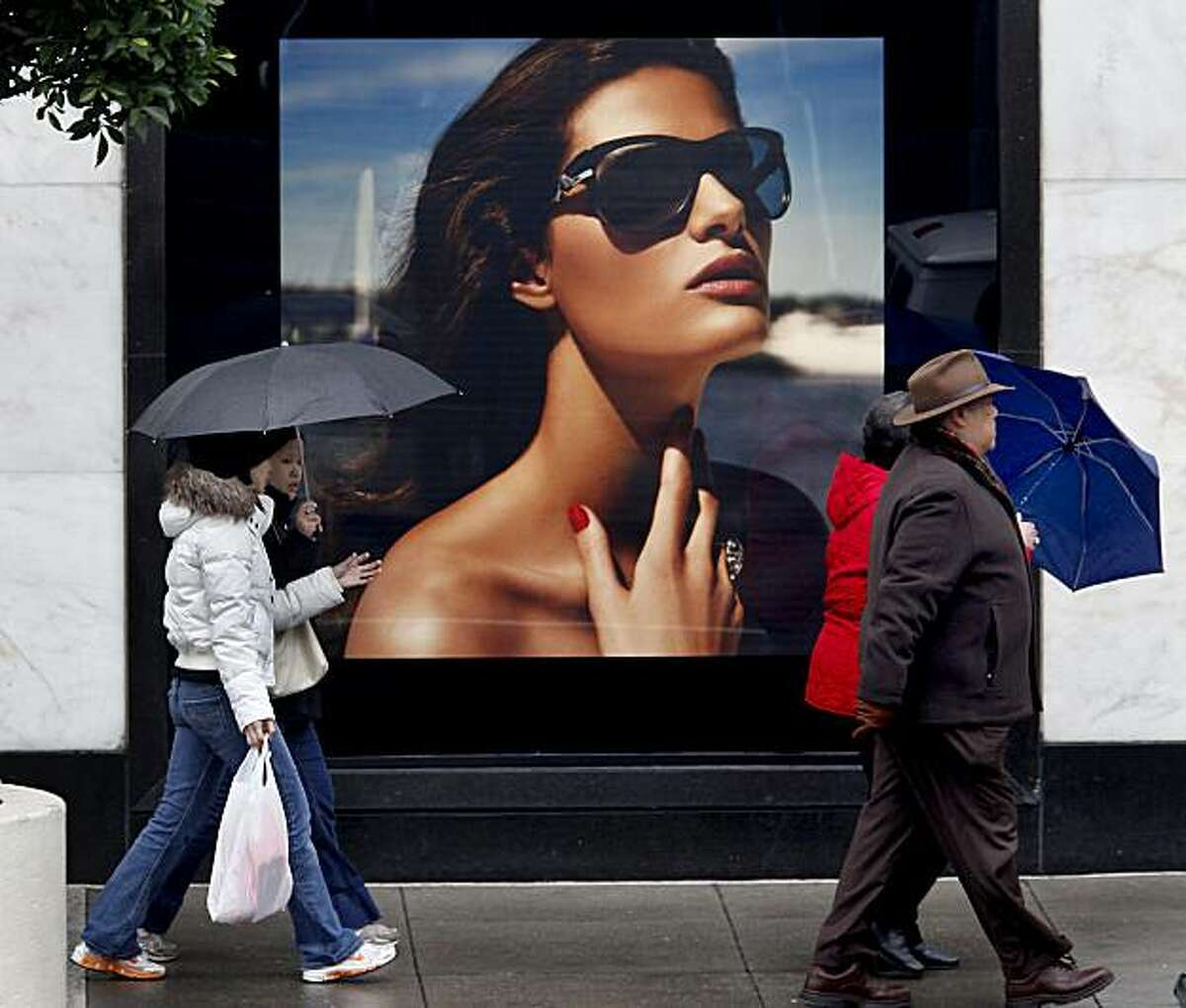 On Geary Street, shoppers walk by a sunny ad for Louis Vuitton. The predicted storms for the week began Sunday, but rainfall was sporadic in downtown San Francisco during the afternoon.