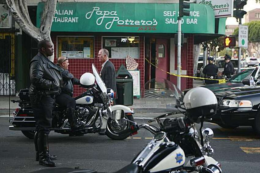 Officials work on 24th Street at Portrero Avenue outside of Papa Potrero's Pizza, the scene of a multiple shooting in San Francisco, Calif. on Sunday, September 20, 2009.