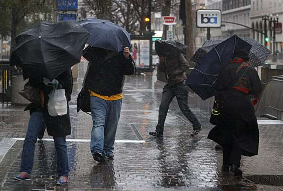 Pedestrians struggle against the wind and rain in downtown Oakland, Calif., on Tuesday. Another strong winter storm battered the Bay Area with more on the way later this week. Photo: Paul Chinn, The Chronicle