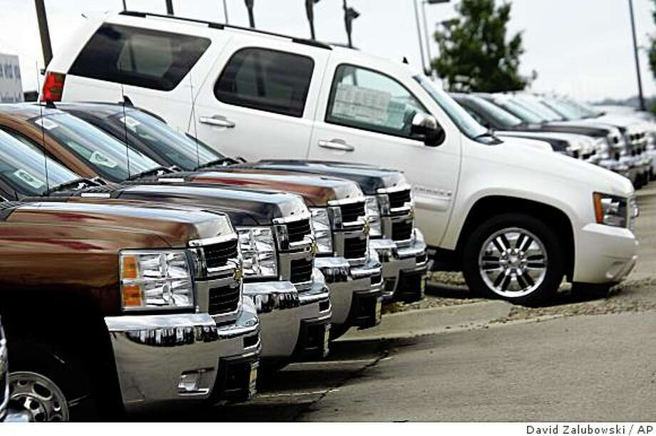 Unsold 2008 Suburbans sit at a Chevrolet dealership in Castle Rock, Colo., on Sunday, July 6, 2008. Shares of General Motors Corp. jumped at market open Monday after the company said it is considering selling some brands, cutting white-collar positions and speeding the introduction of small cars from other markets. (AP Photo/David Zalubowski) Photo: David Zalubowski, AP