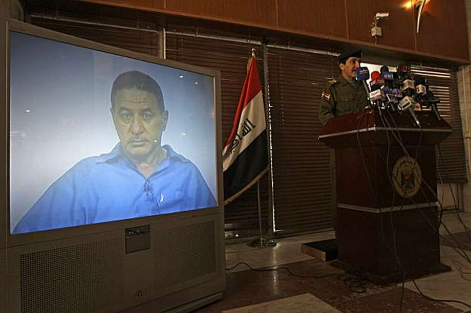 Iraqi military spokesman Maj. Gen. Qassim al-Moussawi, right, stands next to a television display showing Ali al-Azzawi, a senior leader of a militant group linked to al-Qaida, following his arrest in Baghdad, Iraq, Saturday, Jan. 16, 2010. Al-Moussawi identified al-Azzawi as a high-level commander in the Islamic State of Iraq who supervised numerous attacks, including the 2003 bombing of the United Nations' headquarters in Iraq. Photo: Khalid Mohammed, AP