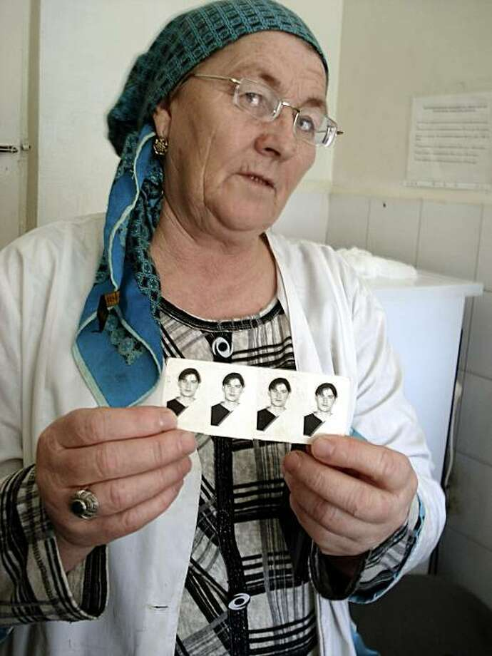** CORRECTS FIRST NAME TO ALISKHAN **This Nov. 12, 2009 photo shows Leila Pliyeva holding photos of her son Aliskhan Pliyev in the city of Nazran in Russia's Ingushetia region. Pliyev was talking on his cell phone with his girlfriend one autumn afternoonwhen two dozen masked men in uniforms stormed into his family's house, grabbed him and began to hustle him away. He hasn't been seen since. Officials in Ingushetia say they don't know anything about Pliyev's abduction, one of scores in recent months thathave caused fresh outrage and grief in a region already scoured by years more than 15 years of armed conflict. Photo: Douglas Birch, AP