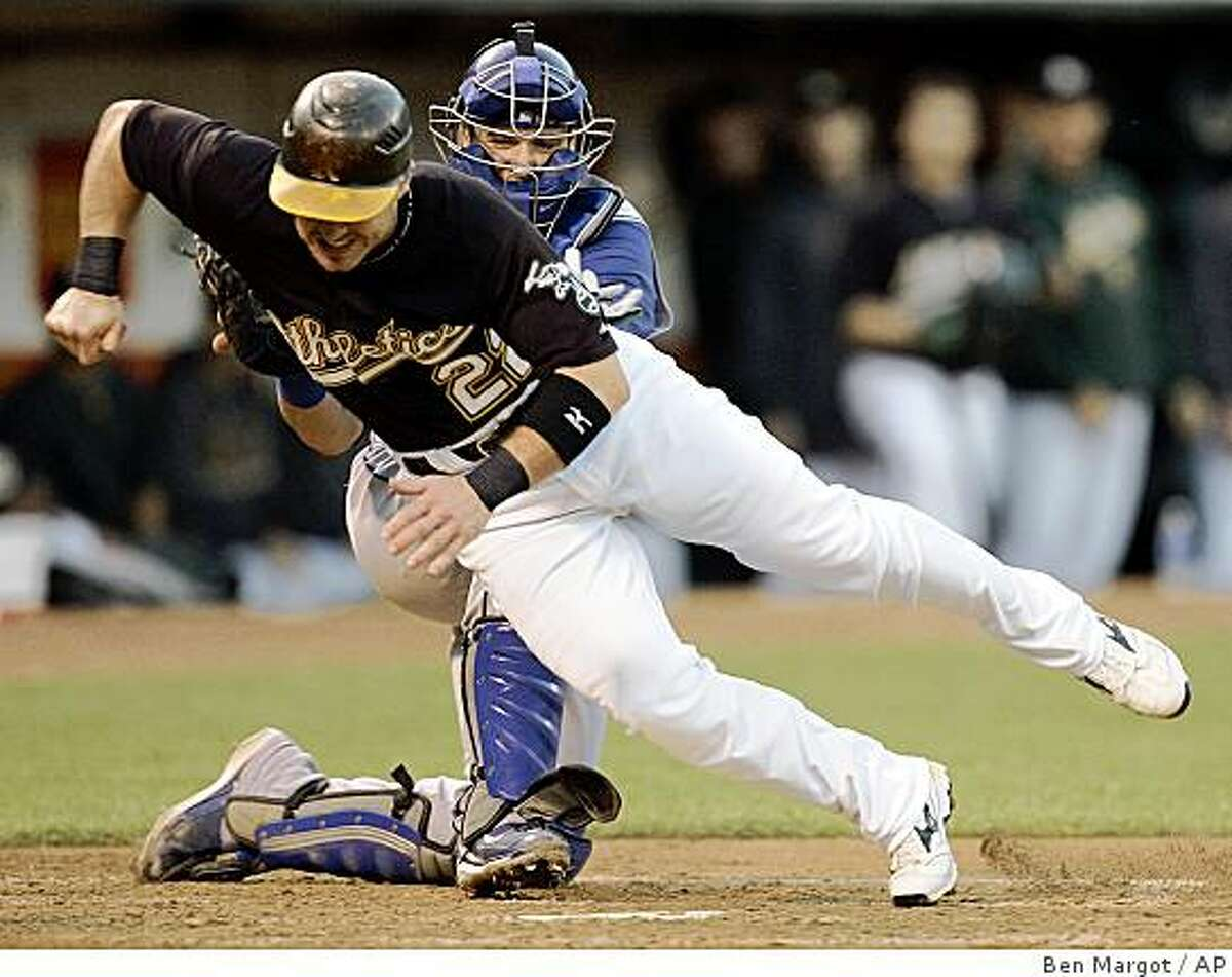 Texas Rangers catcher Jarrod Saltalamacchia, back, tags out Oakland Athletics' Jack Hannahan at home plate in the third inning. (Ben Margot / Associated Press)
