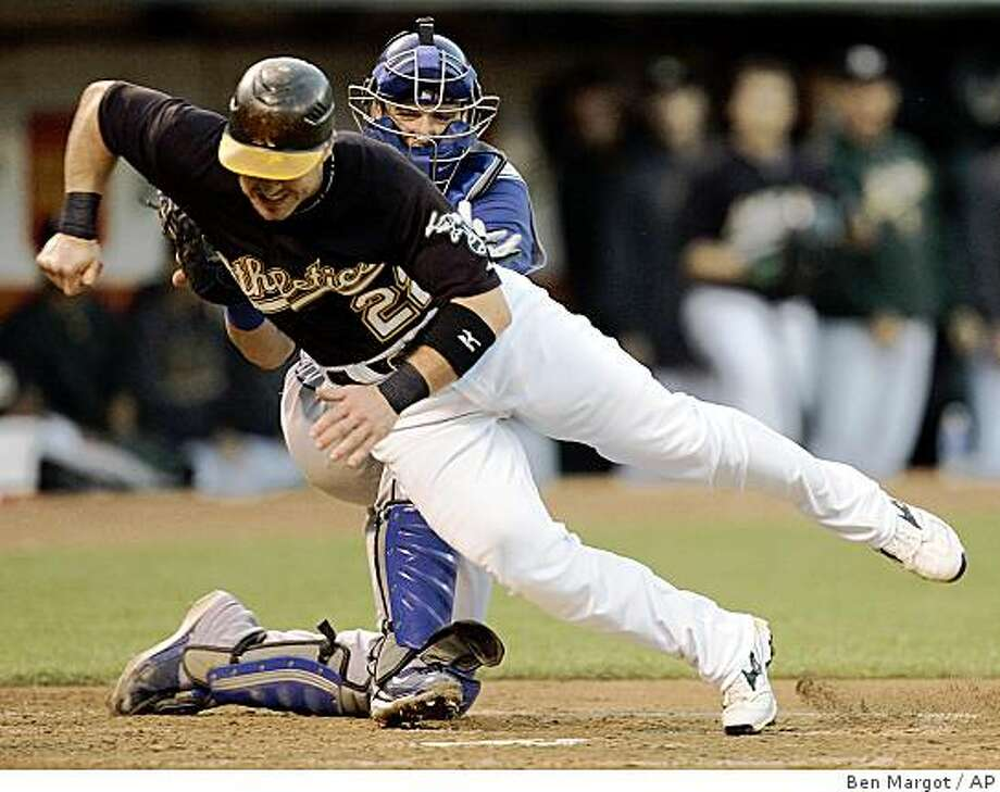 Texas Rangers catcher Jarrod Saltalamacchia, back, tags out Oakland Athletics' Jack Hannahan at home plate in the third inning. (Ben Margot / Associated Press) Photo: Ben Margot, AP