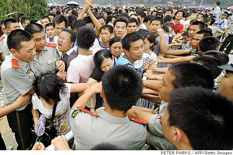 Paramilitary police hold back thousands of people queuing to buy the final batch of Olympic tickets, on sale near the Olympic Stadium in Beijing on July 25, 2008. The final 250,000 Olympic tickets for events in Beijing including athletics, diving, and gymnastics went on sale at 9:00am (0100 GMT). Demand was so high that more than 10,000 people were in the line by July 24 at the main ticket selling centre near the Olympic Stadium and by early July 25 huge reinforcements of police were moved in to maintain order as numbers ballooned to between 40,000 and 50,000.  AFP PHOTO/Peter PARKS (Photo credit should read PETER PARKS/AFP/Getty Images) Photo: PETER PARKS, AFP/Getty Images