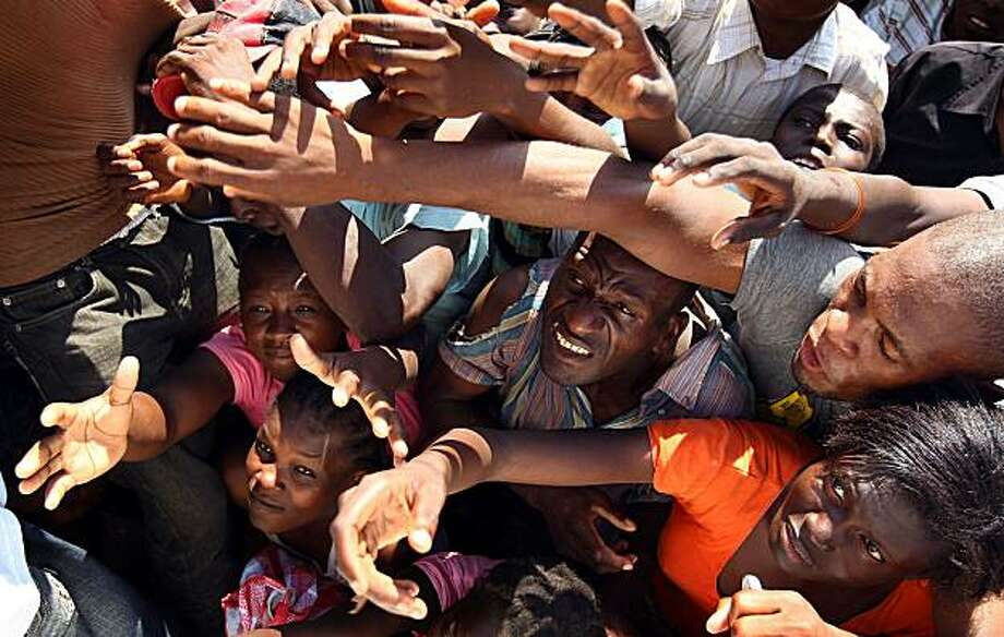 PORT-AU-PRINCE, HAITI - JANUARY 17:  Residents of the Petinville neighborhood of Port-au-Prince reach out to receive food distributed by the United Nations World Food Program on January 17, 2010 in Port-au-Prince, Haiti. Aid agencies are struggling to distribute food as quickly as possible but face major logistical problems in doing so caused by the massive earthquake that took place on January 12. Photo: Win McNamee, Getty Images