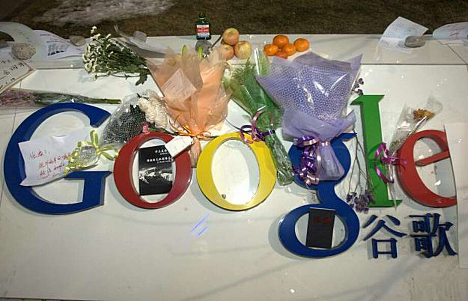 Flowers, fruits and a bottle of liquor, items associated with a traditional Chinese funeral rituals, are placed on Google's logo outside the company's China headquarters in Beijing, Thursday, Jan. 14, 2010. In China's first official response to Google's threat to leave the country, the government Thursday said foreign Internet companies are welcome but must obey the law and gave no hint of a possible compromise over Web censorship. Blue characters at right are a Chinese word for 'Google.' Photo: AP