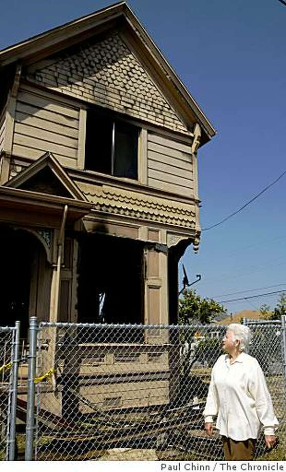 Kathy Kuhner walks past a neighbor's Victorian home that was destroyed by fire at 30th and Magnolia streets in Oakland, Calif., on Thursday, July 24, 2008. Police suspect that drug dealers are to blame for a rash of arson fires in the neighborhood.Photo by Paul Chinn / The Chronicle Photo: Paul Chinn, The Chronicle