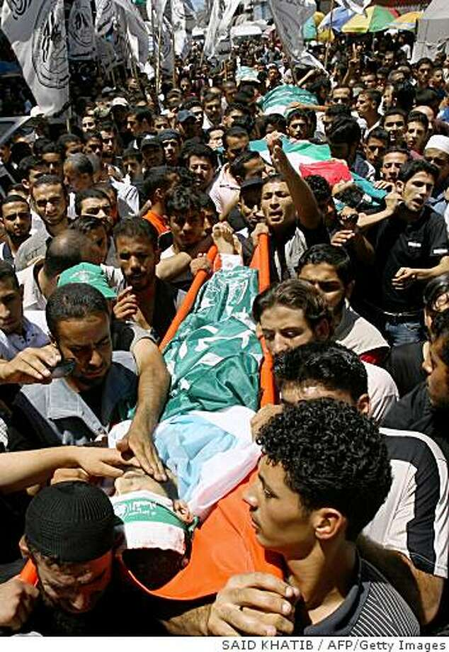 Palestinian mourners carry the bodies of killed Hamas militants through the streets of Gaza City on July 26, 2008, during a funeral after they were caught in an overnight bombing. Hamas-run security forces fanned out across Gaza City today, clashing with rival gunmen and arresting dozens of people after a bomb blast killed five senior Palestinian militants and a girl of five. AFP PHOTO/SAID KHATIB (Photo credit should read SAID KHATIB/AFP/Getty Images) Photo: SAID KHATIB, AFP/Getty Images