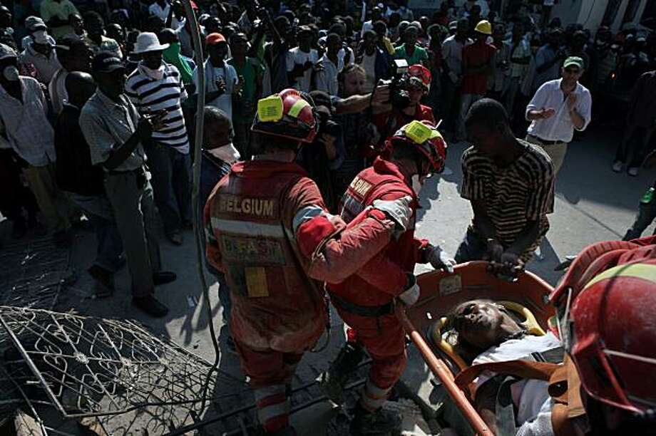 Rescue workers and onlookers applaud as Marie Pierre Louis, 52, is extricated from the rubble of a building in Port-au-Prince, Haiti, on Friday, Jan. 15, 2010. Efforts to deliver desperately needed food, water and medical help to victims of HaitiÕs earthquake intensified on Friday even as the voices of survivors buried underneath mountains of rubble began to fall silent. (Damon Winter/The New York Times) Photo: Damon Winter, New York Times