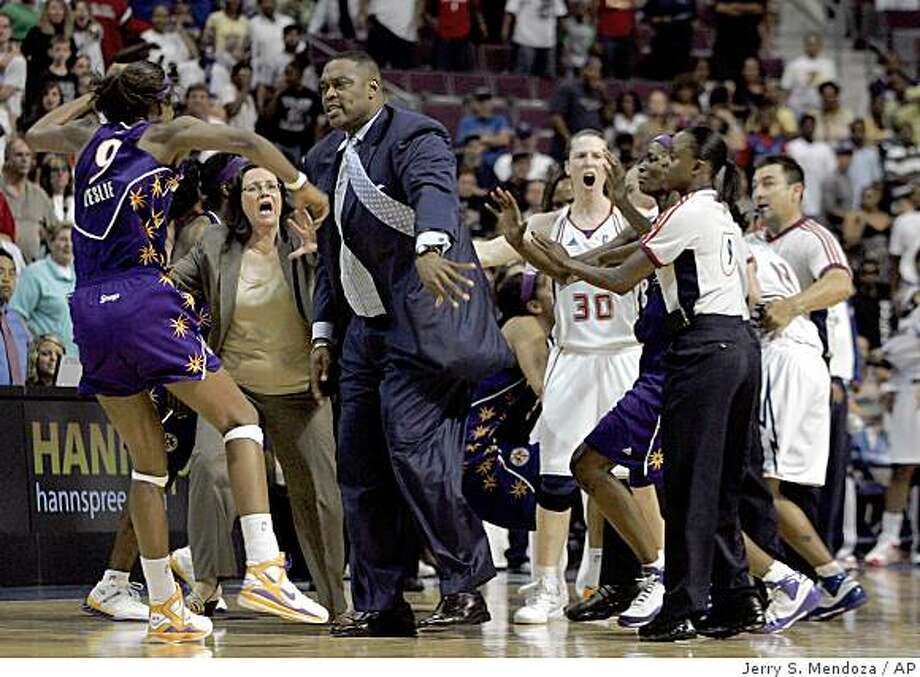 Detroit Shock assistant coach Rick Mahorn, center, pushes Los Angeles Sparks' Lisa Leslie to the ground during a melee in the closing seconds of their WNBA basketball game on Tuesday, July 22, 2008 in Auburn Hills, Mich. Mahorn was ejected from the game and the Sparks won 84-81. Mahorn was attempting to keep Leslie from approaching the Shock bench during a bench-clearing fight in which four were ejected. Associated Press photo by Jerry S. Mendoza Photo: Jerry S. Mendoza, AP
