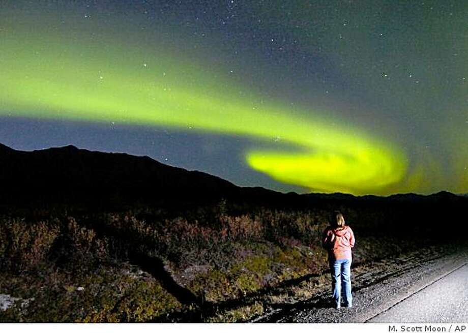 In this Sept. 3, 2006 file photo, a spectator watches the aurora borealis rise above the Alaska Range, in Denali National Park, Alaska.Photo by M. Scott Moon / Associated Press Photo: M. Scott Moon, AP
