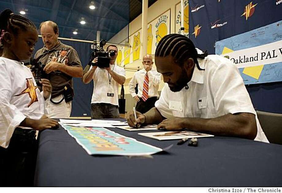 New Warriors player Ronny Turiaf signs autographs for the children as they welcome him to the team on Wednesday, July 23, 2008, Oakland, Calif.New Warriors player Ronny Turiaf makes appearance at Warriors practice facility were he meets with kids and receives his new Warriors jersey on Wednesday, July 23, 2008 Oakland, Calif. Photo by Christina Izzo / The Chronicle Photo: Christina Izzo, The Chronicle