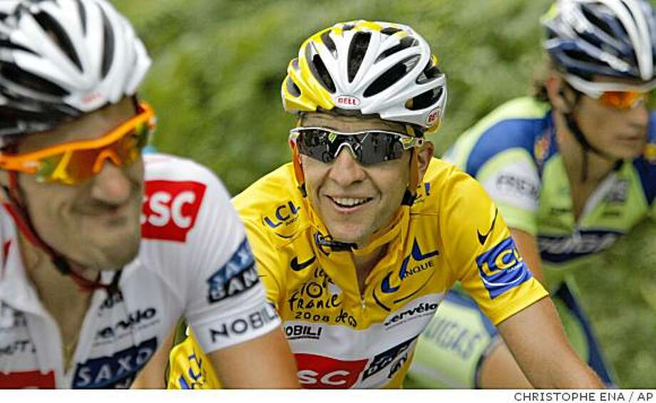 Carlos Sastre of Spain, wearing the overall leader's yellow jersey, center, reacts as he rides with teammate Fabian Cancellara of Switzerland, left, during the 19th stage of the Tour de France cycling race between Roanne and Montlucon, central France, Friday July 25, 2008. (AP Photo/Christophe Ena) Photo: CHRISTOPHE ENA, AP