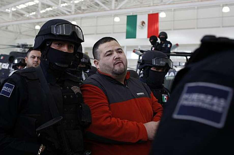 "Teodoro Garcia Simental, known as ""El Teo,"" center, is escorted by federal police after being presented to the press in Mexico City, Tuesday, Jan. 12, 2010. Garcia, one of Mexico's most wanted drug traffickers, was arrested before dawn Tuesday at a home he owned in the city of La Paz on the Baja California peninsula, according to Mexican federal police authorities. Photo: Alexandre Meneghini, AP"