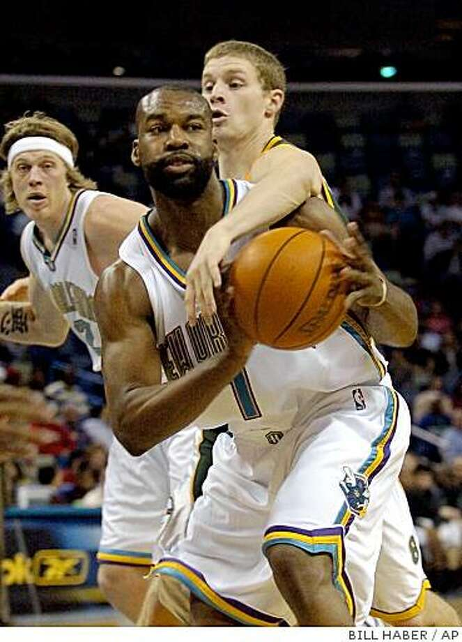 Seattle SuperSonics' Luke Ridnour reaches over the back of New Orleans Hornets' Baron Davis (1) as Chris Andersen looks on during the first half in New Orleans Arena Wednesday night, Feb. 23, 2005. (AP Photo/Bill Haber) Photo: BILL HABER, AP