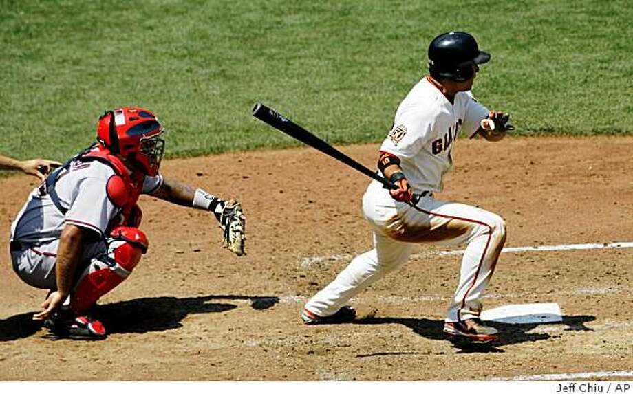 San Francisco Giants' Dave Roberts, right, hits an RBI single off of the Washington Nationals' Tim Redding to score Eugenio Velez in the eighth inning of a baseball game in San Francisco, Thursday, July 24, 2008. The Giants won, 1-0. At left is Nationals' Johnny Estrada. (AP Photo/Jeff Chiu) Photo: Jeff Chiu, AP