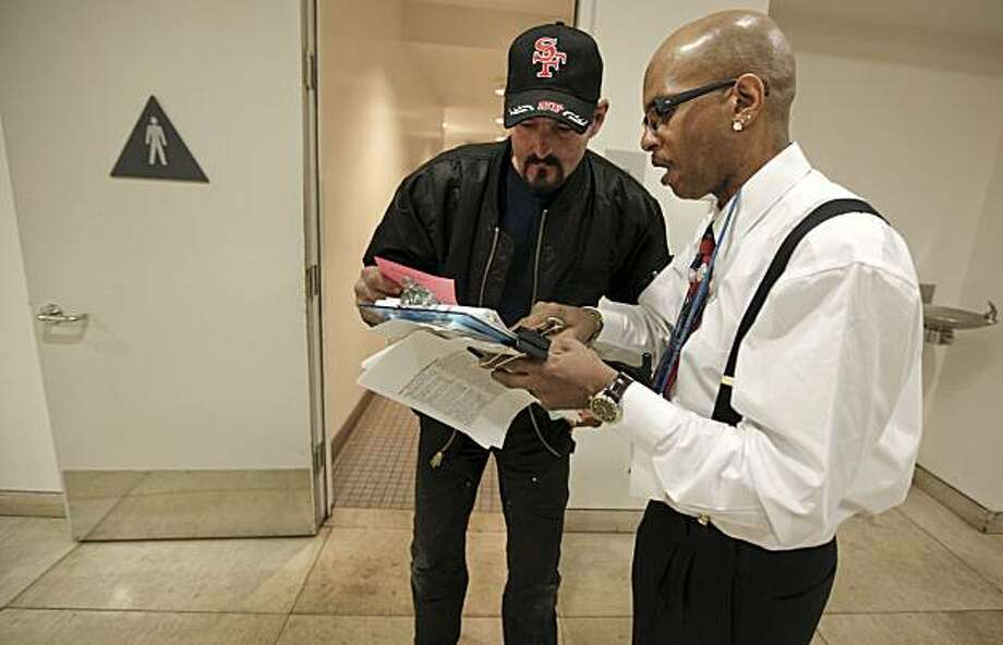 Melvin Morris, (right)  a Health and Safety Associate for San Francisco's Main Public Library, is in charge of monitoring the public restrooms as well as briefing the homeless on the various programs available to them in San Francisco, Ca.  Morris introduces Robert Lewis to several services available to him on Tuesday December 9, 2009. Once homeless himself he is the first one to take the associate position. Photo: Michael Macor, The Chronicle