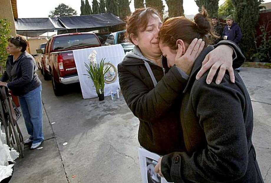 Close relatives of Alvaro Ayala cry and hug each other near the spot he was gunned down Sunday. Photo: Brant Ward, The Chronicle