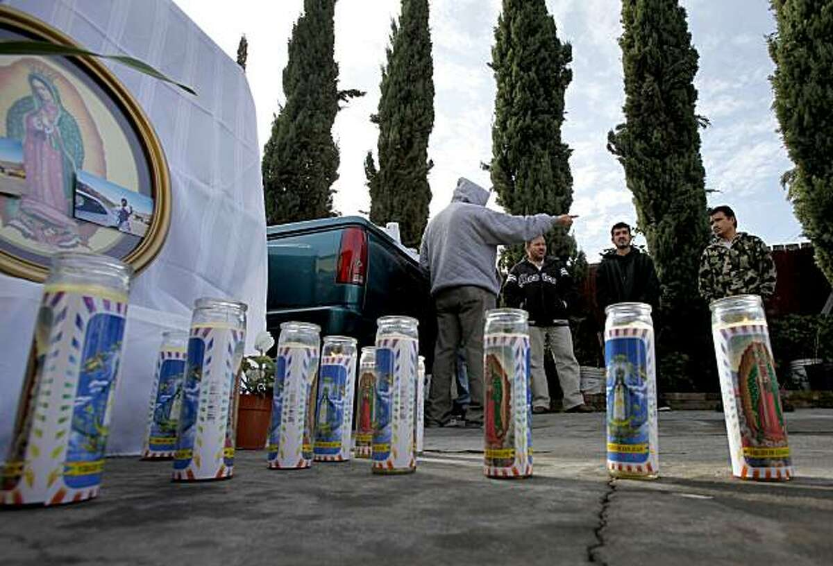 Friends of Alvaro Ayala gather near a memorial where Ayala was gunned down in Oakland on Sunday.