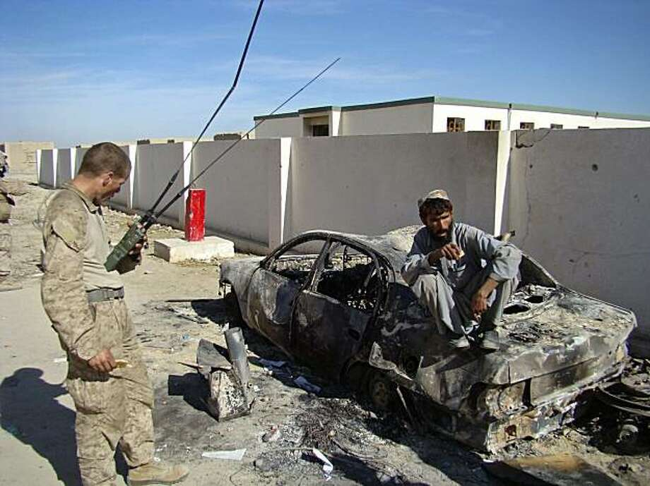 A US Marine talks Wednesday Jan  13 2010 to  an Afghan sitting on a car destroyed the previous day in a clash in the city of Laki,  in Helmand province's Garmsir district, south of Kabul Afhanistan. A spokesman for the provincial governor in Helmand, saidinsurgents organized the Tuesday protest that left six civilians dead and seven others wounded. A NATO official, who spoke Wednesday on condition of anonymity because of the sensitivity of the issue, said they are still are conflicting reports about theprotest. Photo: Abdul Khaleq, AP