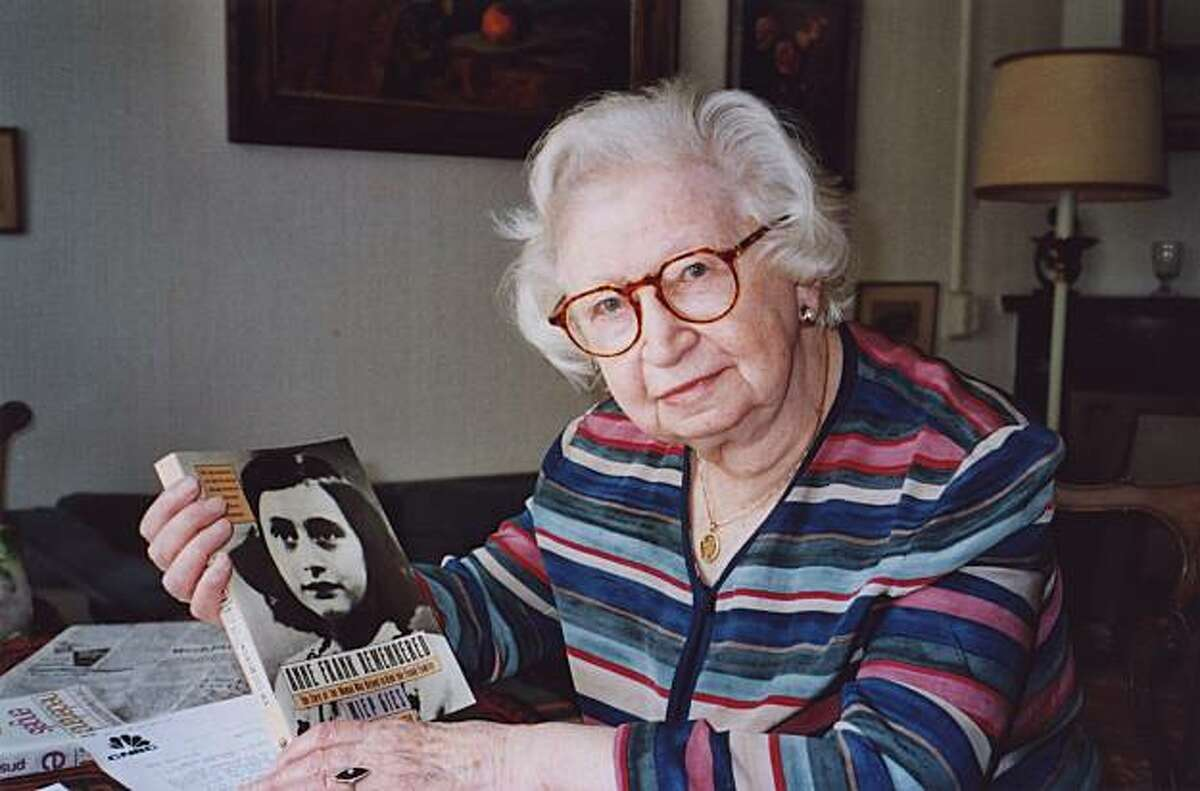 """FILE - In this 1998 photo Miep Gies displays a copy of her book """"Anne Frank Remembered"""" at her apartment in Amsterdam, Netherlands. Anne Frank called them the Helpers. They provided food, books and good cheer while her family hid for two years from the Nazis in a tiny attic apartment. On Sunday, Feb. 15, 2009, the last surviving helper, Miep Gies, celebrates her 100th birthday, saying she has won more accolades for helping the Frank family than she deserved as if, she says, she tried to save all the Jewsof occupied Holland. The Anne Frank Museum says Gies, who helped the teenage diarist's family hide from the Nazis, died Monday Jan. 11, 2010. She was 100."""
