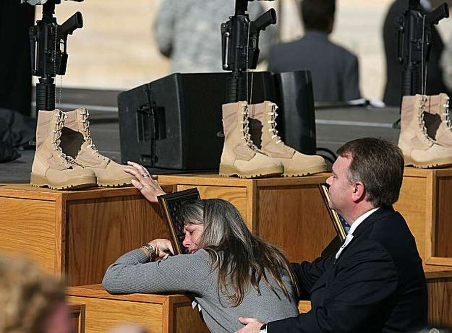 A family member hugs the picture and touches the boots of a fallen soldier, Pfc. Aaron Nemelka, during a memorial honoring the 13 victims of a mass shooting at Fort Hood held at U.S. Army's III Corps headquarters at Fort Hood, Texas, Tuesday, Nov. 10, 2009. (AP Photo/Rodolfo Gonzalez, Pool) Photo: Rodolfo Gonzalez, AP