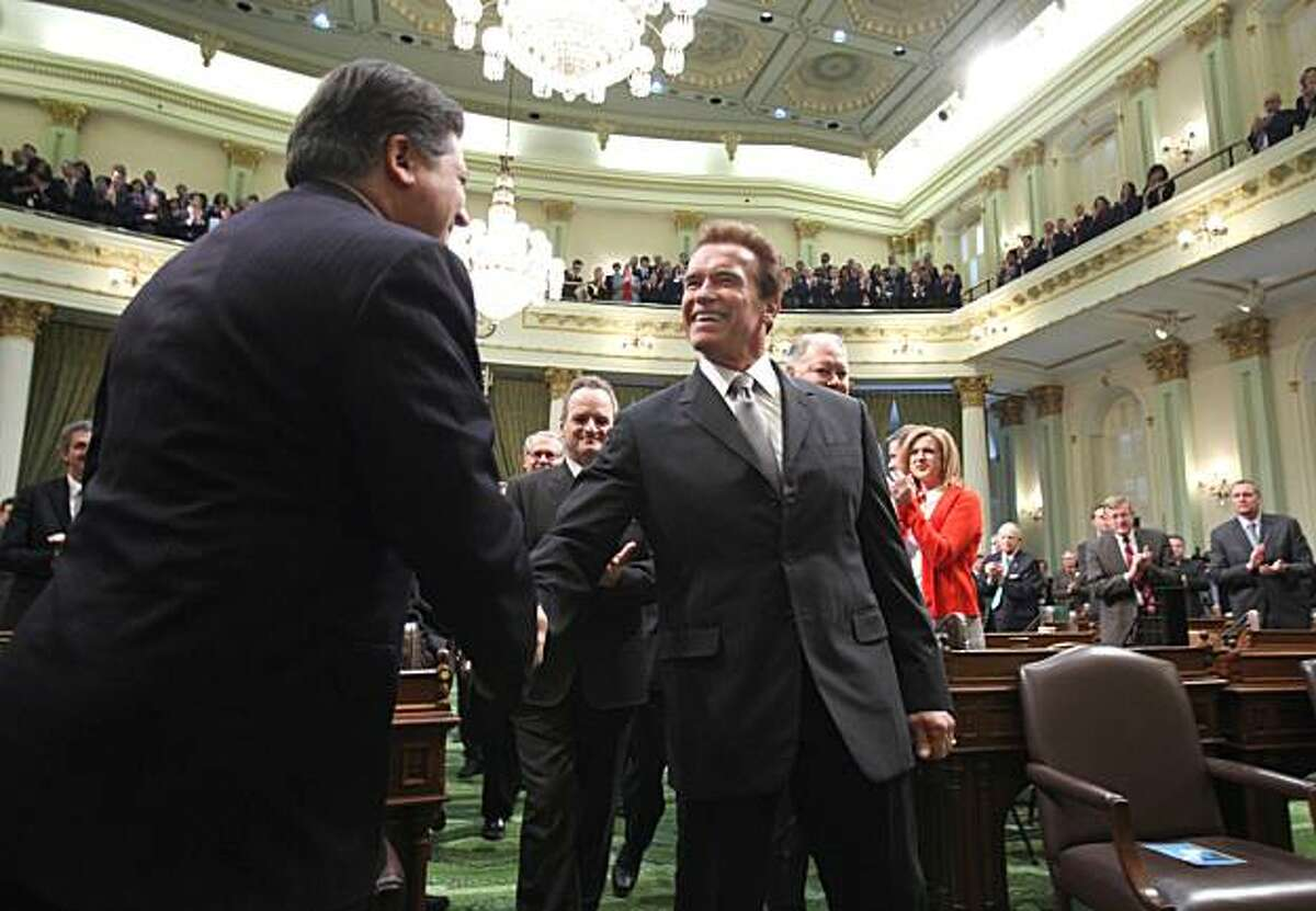 Gov. Arnold Schwarzenegger shakes hands with former Assembly Speaker Robert Hertzberg, D-Los Angeles, as he walks to the podium to deliver his final State of the State address before a joint session of the Legislature at the Capitol in Sacramento on Wednesday.