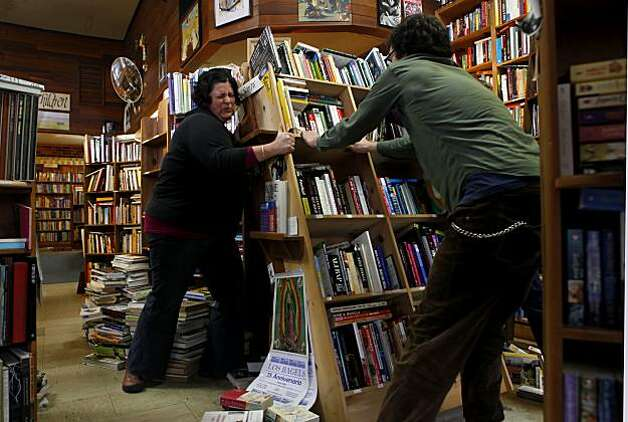 Gabriella Aragon, left, and Aber Miller lift a collapsed bookshelf Sunday at the Booklegger in Eureka. The Booklegger lost four big windows and several bookshelves were knocked over during Saturday's 6.5 earthquake. Photo: Lacy Atkins, The Chronicle