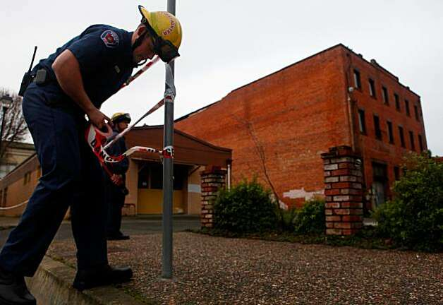 Humboldt County firefighter Brandon Johnson ties danger lines around the former Old Town Bar and Grill in Eureka on Sunday. Part of the roof collapsed onto a neighboring building during Saturday's 6.5 earthquake. Photo: Lacy Atkins, The Chronicle