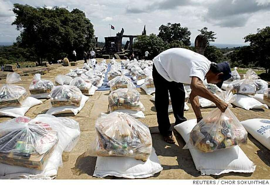 A Cambodian worker arranges food donated by the royal palace for soldiers and villagers at Preah Vihear temple, 245km (152 miles) north of Phnom Penh, July 22, 2008. Southeast Asian foreign ministers nudged Thailand and Cambodia on Tuesday to resolve a stand-off over an ancient temple on their border before bullets start flying.  REUTERS/Chor Sokunthea (CAMBODIA) Photo: CHOR SOKUNTHEA, REUTERS