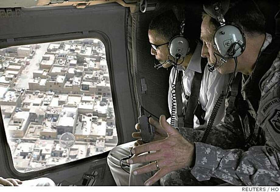 Gen. David H. Petraeus (R) explains security improvements in Sadr City while giving an aerial tour of Baghdad to Senators Barack Obama (D-IL), Jack Reed (D-RI) and Chuck Hagel (R-NE) July 21, 2008.  REUTERS/Lorie Jewell/Multi-National Forces Iraq Public Affairs/Handout   (IRAQ).  FOR EDITORIAL USE ONLY. NOT FOR SALE FOR MARKETING OR ADVERTISING CAMPAIGNS. Photo: HO, REUTERS