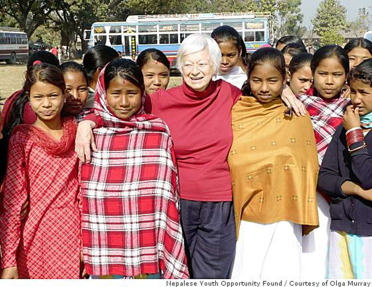 Olga Murray 83 is largely responsible for eradicating female child slavery in a small part of western Nepal by offering families a pig to raise instead of selling their daughters. She is shown here with some of the young women she saved and was later able to get into schools.