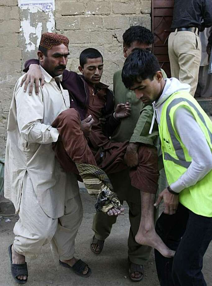 Pakistani volunteers carry an injured person after an explosion in Karachi, Pakistan on Friday, Jan. 8, 2010. A blast apparently caused by explosives stored in a house in the southern Pakistani city of Karachi killed at least seven people, some of whom may have been militants, police said. Photo: Fareed Khan, Associated Press