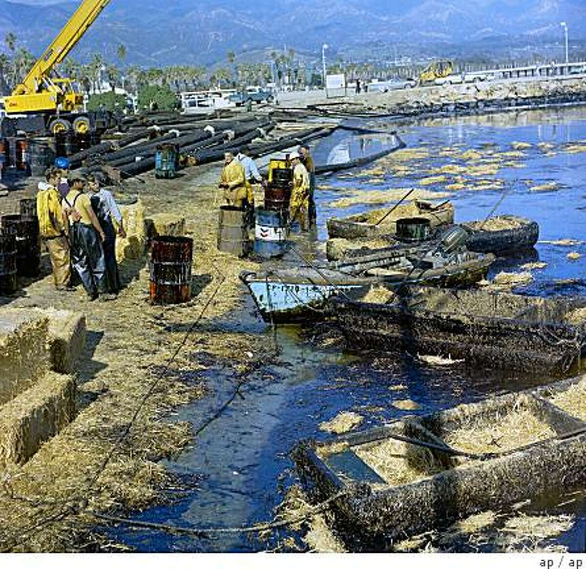Workmen using pitchforks and shovels attempt to clean up oil-soaked straw from the beach at Santa Barbara Harbor, Calif. Feb. 7, 1969 after oil leaking from an off-shore well for over a week covered local beaches. (AP Photo)