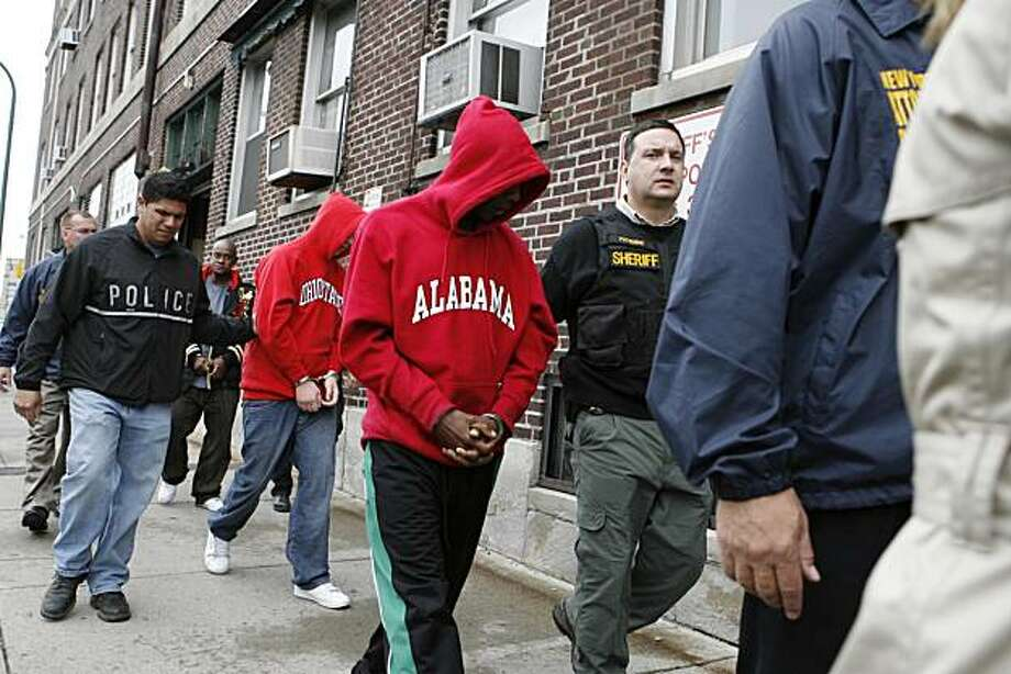 FILE - In this Sept. 29, 2009 file photo, Erie County sheriff's officials escort some of the 12 employees of a debt collection firm who were charged with extortion to the Erie County Holding Center in Buffalo, N.Y. Buffalo's status as a national hub for collectors has been a rare economic bright spot in a place where 30 percent of the people live in poverty. It has also become a center for some of the worst elements in the debt business.  (AP Photo/The Buffalo News, Harry Scull Jr) MANDATORY CREDIT Photo: Harry Scull Jr, AP