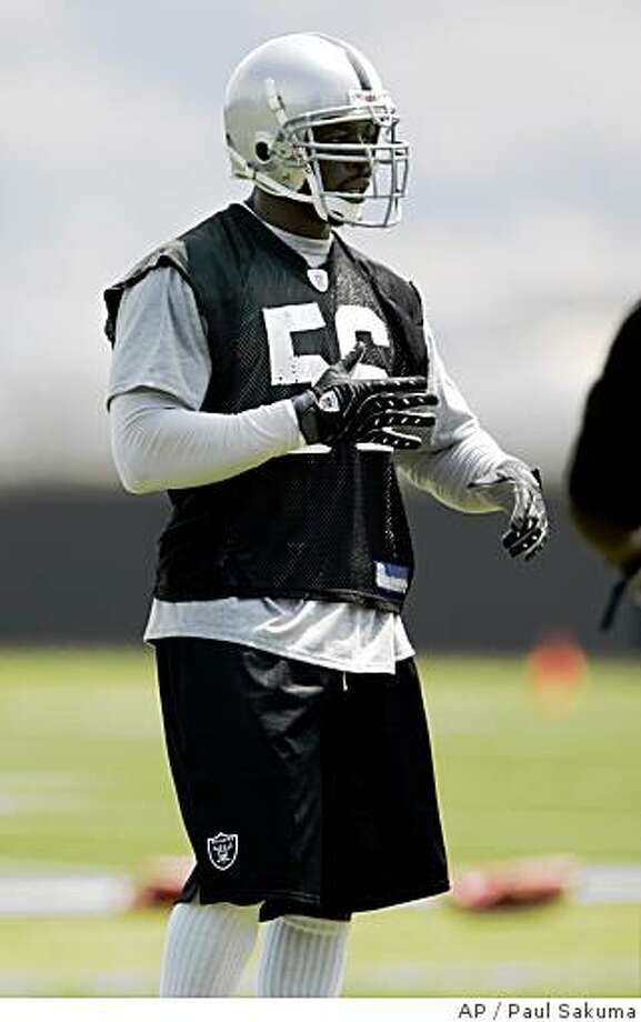 Oakland Raiders defensive end Derrick Burgess works out at the NFL football team's minicamp in Alameda, Calif., Tuesday, June 3, 2008. Burgess didn't take long to show his impact. He burst around the end on one play and was poised to deliver a big hit on quarterback JaMarcus Russell if this had been a game rather than a practice. Burgess said it was good to be back competing with his teammates after being gone the past five months. (AP Photo/Paul Sakuma) Photo: Paul Sakuma, AP