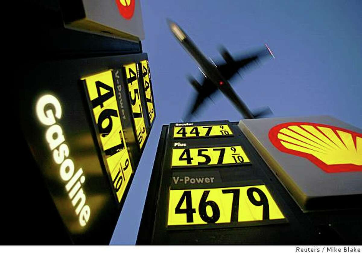 Gasoline prices are advertised at a gas station near Lindbergh Field as a plane approaches to land in San Diego, California in this June 1, 2008 file photo. To match Reuters Witness story OIL/TAXI in which, Daniel Fineren, who is a senior energy correspondent, describes his recent encounter with a Spanish taxi driver on the way home from the World Petroleum Congress. To match Reuters Witness story OIL/TAXI. REUTERS/Mike Blake (UNITED STATES)