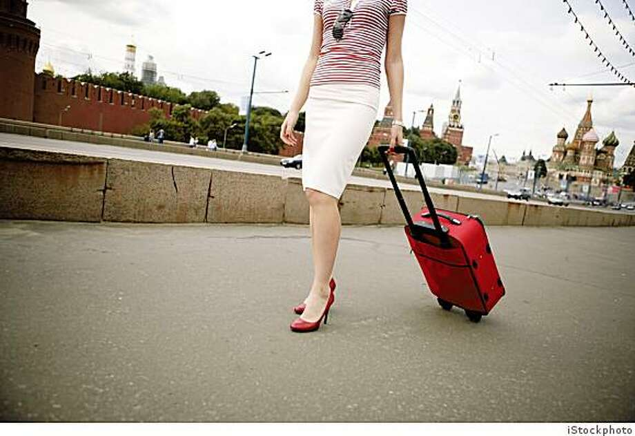 A woman walking with a suitcase in Moscow, from iStock, to be used for the article about packing light.